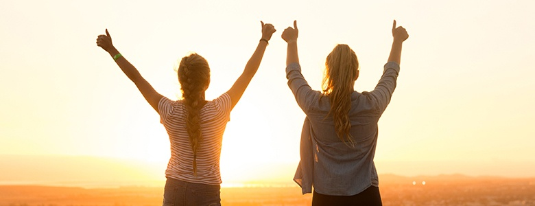 two girls holding their thumbs up
